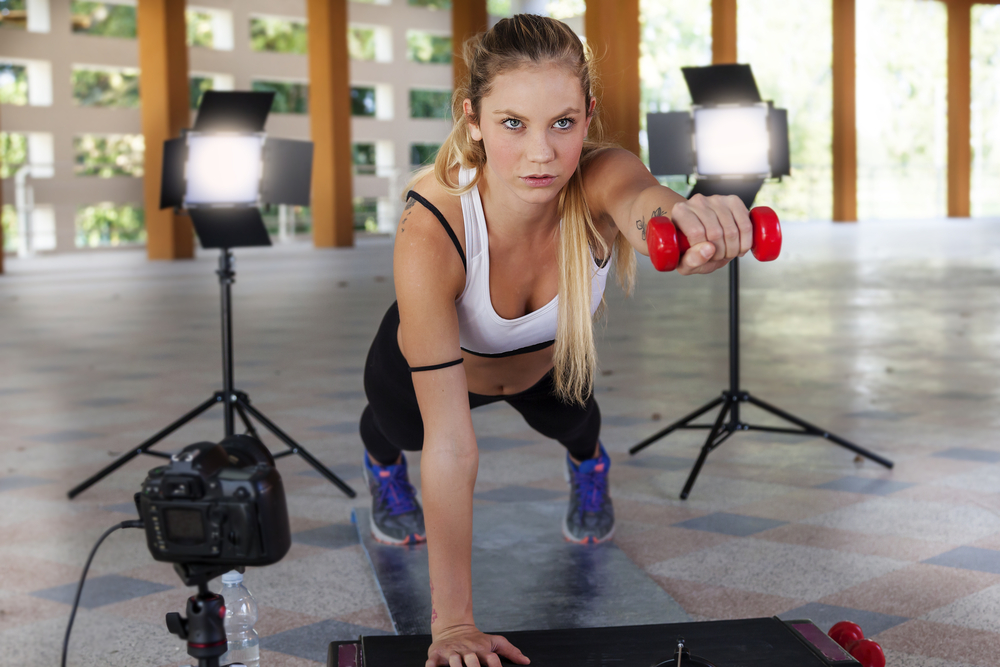 Young woman doing a plank with a dumbbell in one hand, while cameras and lights surround her for her social media.