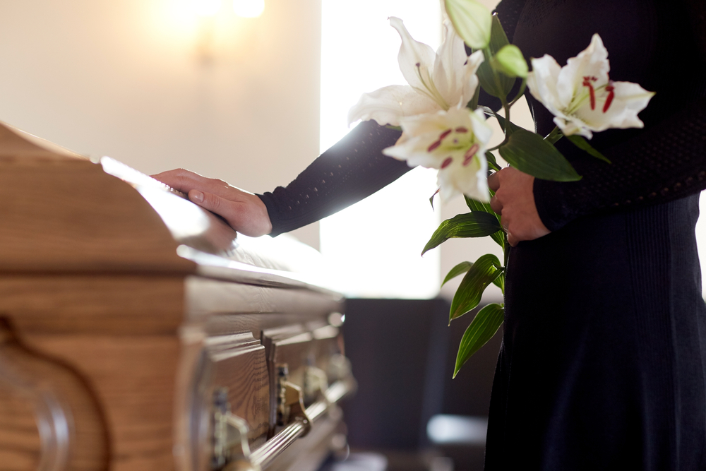 Woman in black dress standing with hand on casket in funeral home, holding white lilies.