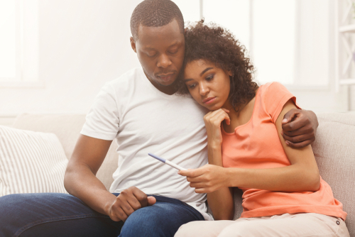 Sad African American Couple Sitting On A Couch Indoors Looking At A Pregnancy Test